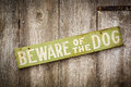 Beware of dog sign on old worn wood fence wooden Stock Photo