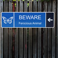 Beware Horizontal Blue Sign on Old Wood Fence Royalty Free Stock Photo