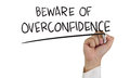 Beware of overconfidence business concept image a hand holding marker and write isolated on white Royalty Free Stock Image