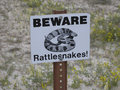 Beware rattlesnakes sign warning of that might be hiding below a boardwalk at badlands national park Royalty Free Stock Image