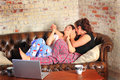 Bff telling secrets at slumber party two pretty brunette teenage girls with coffee and a computer on the table a on the couch in Stock Image