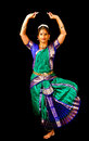 Bharatanatyam dancer young woman in traditional sari dancing classical indian dance on a black background Royalty Free Stock Photography