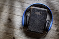 Bible and headphones holy concept for modern religious education podcast or help with hearing for blind studying Royalty Free Stock Photo