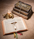 A bible open on a table with burning candle Stock Images
