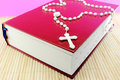 Bible and rosary over an old red Stock Photos