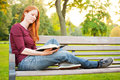 Bible study in a park woman sitting on bench and reading Stock Photos