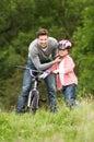 Bici del paseo de teaching son to del padre en campo Imagen de archivo libre de regalías