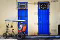 Bicitaxi driver parked up infront of two blue doors in the shade taking a rest this cuban bicycle taxi is waiting for fare or Stock Photography