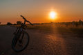stock image of  Bicycle on the background of a road and sunset in the background vineyard
