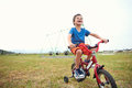 Bicycle boy young learning to ride a bike with training wheels in park Royalty Free Stock Photography