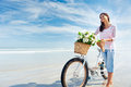 Bicycle flower woman with and flowers in basket smiling carefree and happy Royalty Free Stock Images