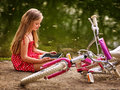 Bicycle girl recreation and watch tablet pc sits near water. Royalty Free Stock Photo