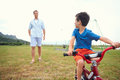 Bicycle lessons young boy learning to ride a bike with training wheels in park Stock Image