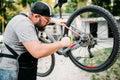 Bicycle mechanic adjusts back disk brakes Royalty Free Stock Photo