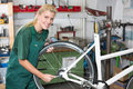 Bicycle mechanic repairing wheel on bike with wrench changing in workshop Royalty Free Stock Images