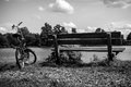 Bicycle near bench and pond in park. Black-white photo Royalty Free Stock Photo