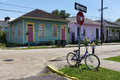 Bicycle parked at a stop sign in front of a row of colorful houses in a street of the city of New Orleans in Louisiana.