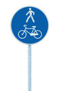 Bicycle and pedestrian lane road sign on pole post, large blue round isolated bike cycling and walking walkway footpath route Royalty Free Stock Photo