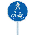Bicycle and pedestrian lane road sign on pole post, large blue round isolated bike cycling walking walkway footpath trail route Royalty Free Stock Photo
