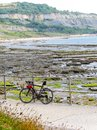 Bicycle at rest on railing by ocean and mountian backdrop Royalty Free Stock Photo