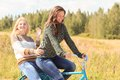 Bicycle ride of two attractive girls in countryside Royalty Free Stock Images