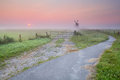 Bicycle road to windmill in fog at sunrise Stock Images