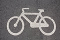 Bicycle sign white image on black asphalt road closeup Stock Images
