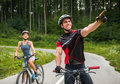 Bicycle sport happy carefree couple riding on bicycles at the road man pointing away Royalty Free Stock Photo