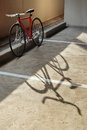 Bicycle standing in the parking lot and its shadow red single speed Royalty Free Stock Image