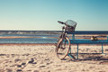 Bicycle stands near bench on beach against sea. Royalty Free Stock Photo