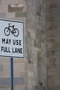 Bicycle street sign with a black bicycle close to a gray wall saying may use full lane in the background miami Stock Image