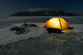 Bicycle tourists' winter camp – orange tent and bikes on the surface of frozen lake night scene Royalty Free Stock Photos