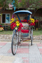 Bicycle tricycle decorated with colorful flowers in the park Stock Image