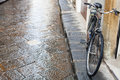 Bicycle on wet street in Florence city in rain Royalty Free Stock Photo