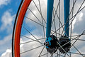 Bicycle wheel detail blue bike frame and orange on a background of sky Royalty Free Stock Photography
