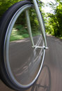 Bicycle wheel in motion on street Stock Photography