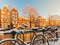 Bicycles covered with snow during winter in amsterdam alongside a canal Royalty Free Stock Images