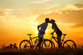 Bicycles kiss of romantic young couple on against sunset Royalty Free Stock Images