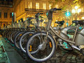 Bicycles in paris lines waiting to be picked at the station for a romantic ride city by night public velib bicycle sharing Royalty Free Stock Photos