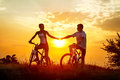 Bicycles romantic young couple on against sunset Stock Photography