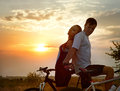 Bicycles silhouette of romantic young couple on sporty against sunset Stock Photos