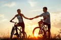 Bicycles silhouette of young couple on sporty against sunset Stock Photo