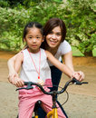 Bicycling asian girl learns to ride bicycle Stock Photo