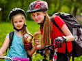 Bicycling girls with rucksack eating ice cream cone in park. Royalty Free Stock Photo