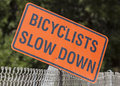 Bicyclists slow down sign weathered in a urban city park Stock Image