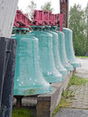 Big bells five standing on wooden log Royalty Free Stock Photos