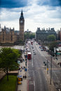 Big ben across the bridge and westminster in london with traffic and many people crossing Stock Photo