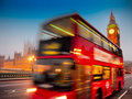 Big ben houses parliament red double decker bus passing dusk Royalty Free Stock Image