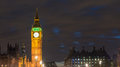 Big ben one of the most prominent symbols of both london and en england as shown at night along with lights cars passing Royalty Free Stock Image