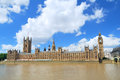 Big ben tower and houses of parliament in london under blue and clocktower cloudy sky Royalty Free Stock Image